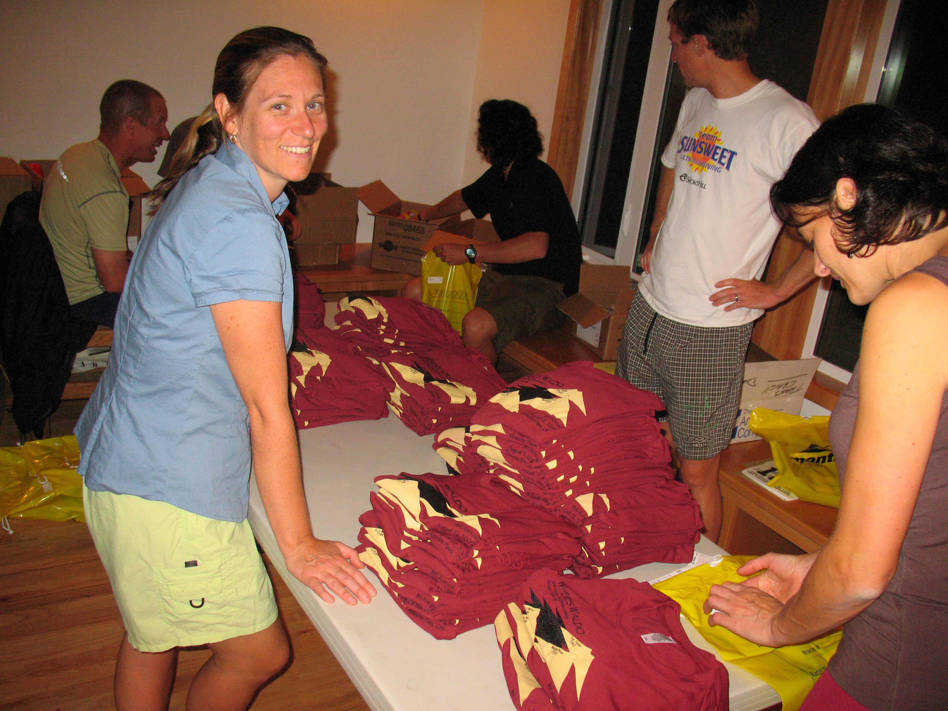 Hannah Shallice and others folding race shirts